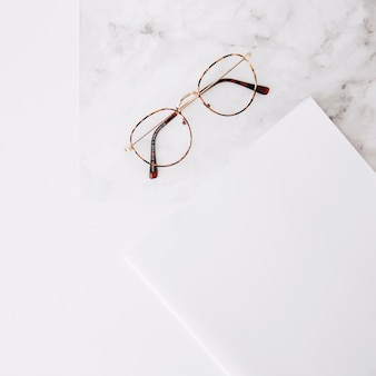 Eyeglasses and white paper on textured white backdrop
