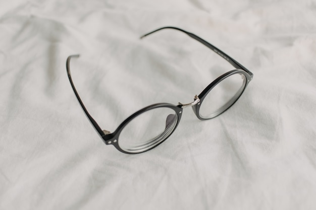 Eyeglasses with black plastic temple on white bed sheet.