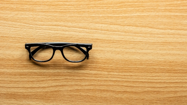 Eyeglasses on wooden desk.