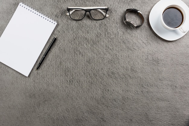 Eyeglasses; wrist watch; coffee cup and spiral notepad with pen on gray table top