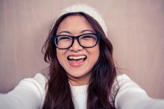 Eyeglasses азиатской женщины нося усмехаясь на камере