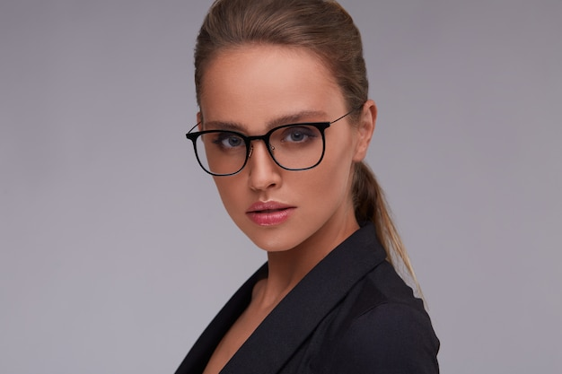 Элегантная серьезная женщина в квадратных eyeglasses. взрослый красивая деловая женщина в костюме