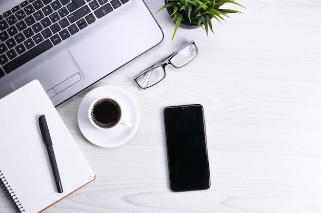 Взгляд сверху места для работы офиса, деревянного стола стола с тетрадью компьтер-книжки, клавиатуры, ручки, eyeglasses, телефона, тетради и чашки кофе.