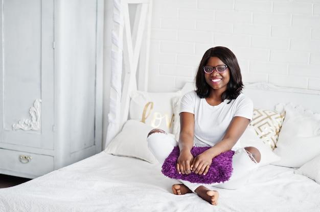 Милая афро-американская женщина в eyeglasses представила в комнате, сидя на кровати с фиолетовой подушкой.