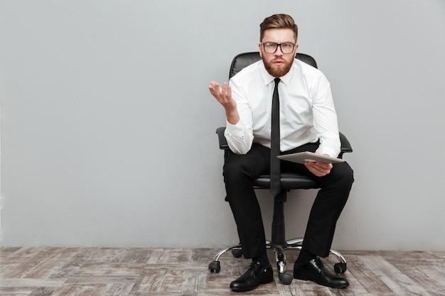 Раздражанный расстроенный бизнесмен в eyeglasses держа таблетку пк