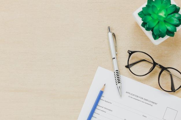 Вид сверху рабочего стола бизнес-справочника. подача заявки на форму задания и ручка карандашом eyeglasses дерево на деревянном столе фон с копией пространства.