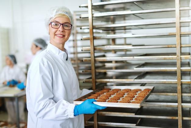 Усмехаясь белокурый женский работник с eyeglasses и в стерильной форме кладя поднос с очень вкусными печеньями в шкаф.