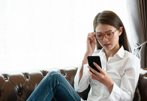 Eyeglasses молодой азиатской женщины нося пробуя прочитать текст телефона.