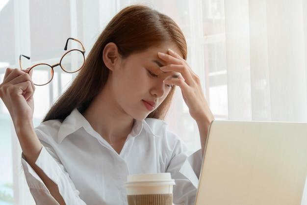 Утомленная или подавленная азиатская женщина сидя за ее компьтер-книжкой с ее руками держа eyeglasses