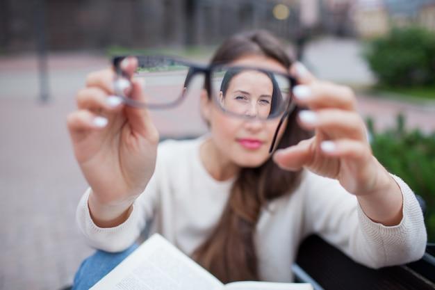 Портрет крупного плана женщины с eyeglasses в руке.