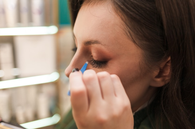まつげエクステ。美しい女性の目に人工まつげを適用するピンセットでマスターの手。長い偽まつげと女性の顔のクローズアップ。