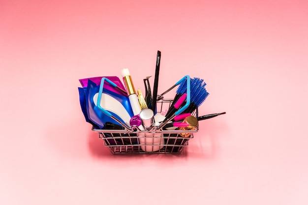 Eyelash extension kit in a small grocery basket on pink background.