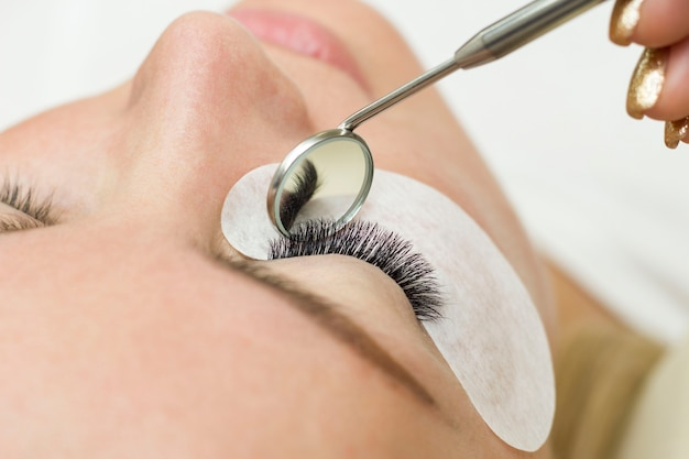 Eyelash extension procedure. beautiful woman with long eyelashes in a beauty salon. eyelashes close up. a mirror in the hands of a master