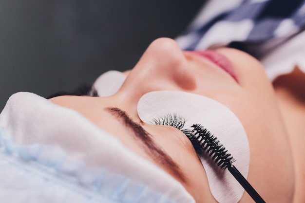 Eyelash extension procedure. close up view of female eye with long eyelashes. stylist holding pink tweezers, tongs and making lengthening lashes. macro, selective focus. beauty concept. treatment.