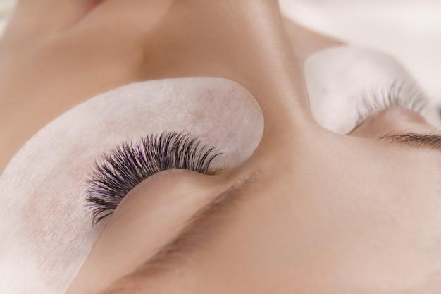 속눈썹 연장 절차. 긴 속눈썹, 부드러운 건강 한 피부와 아름 다운 여성의 눈의 뷰를 닫습니다.