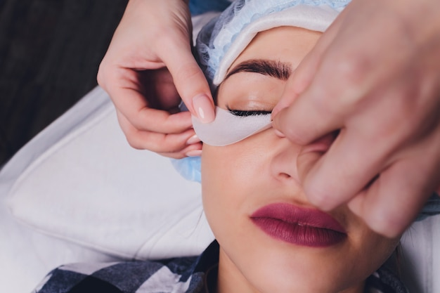 まつげエクステ手順。長いまつげと女性の目のビューを閉じます。ピンクのピンセット、トングを持ち、長く伸びるまつげを作るスタイリスト。マクロ、セレクティブフォーカス。美容コンセプト。処理。