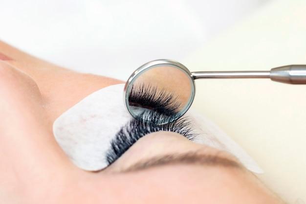 Процедура наращивания ресниц. женский глаз с длинными ресницами. закройте вверх. зеркало в руках мастера