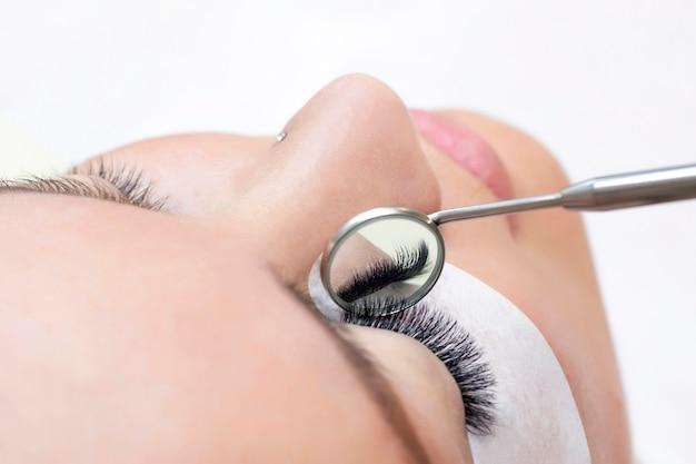 Процедура наращивания ресниц. женский глаз с длинными ресницами. закройте вверх. зеркало в руках