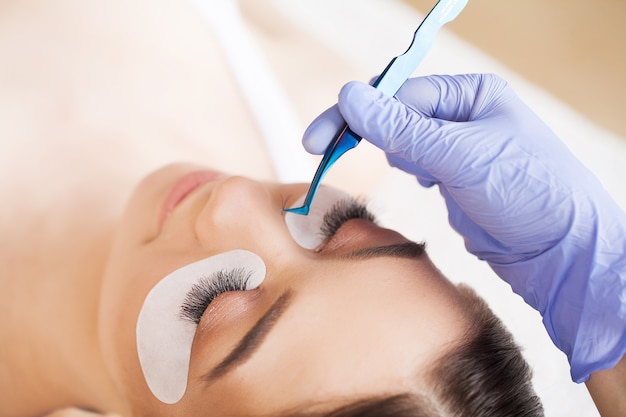 Eyelash extension procedure. professional stylist lengthening female lashes.