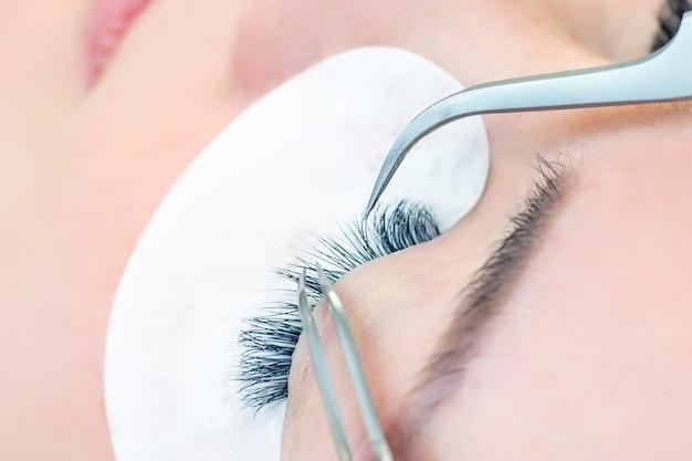 Eyelash extension procedure using tweezers