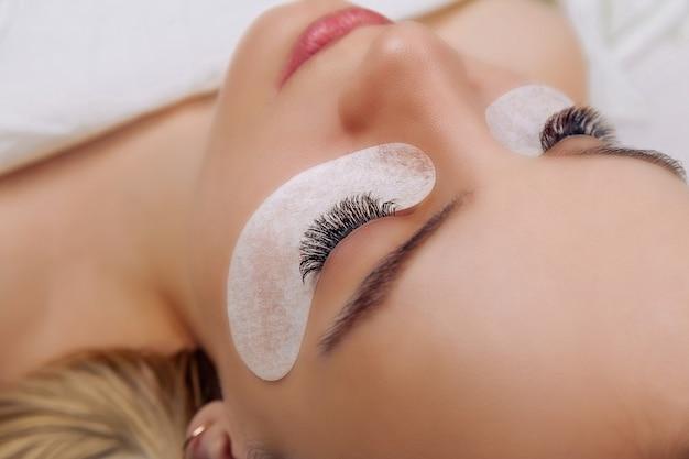 Eyelash extension procedure woman eye with long blue eyelashes close up selective focus