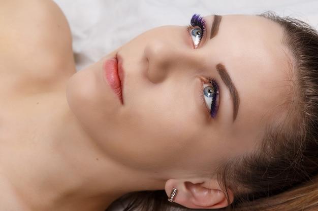 長い青いまつげオンブル効果を持つまつげエクステ手順女性の目は、選択的な焦点を閉じます