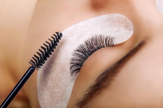 Eyelash extension procedure woman eye with long blue eyelashes