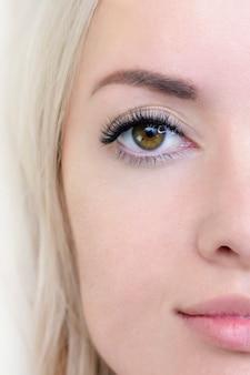Процедура наращивания ресниц. женский глаз с длинными ресницами. закройте вверх. вертикальное фото