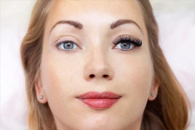 Процедура наращивания ресниц. женский глаз с длинными ресницами. закрыть вверх