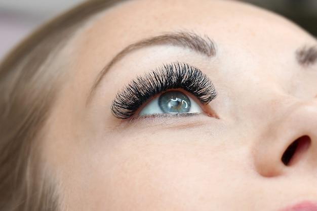 まつげエクステの手順。長いまつげを持つ女性の目。閉じる Premium写真