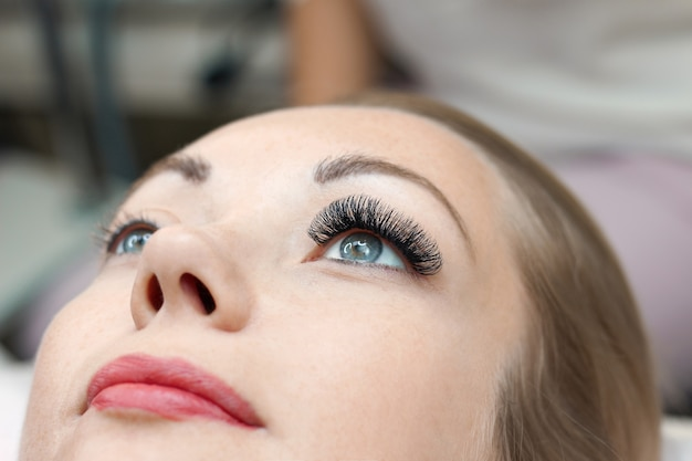 まつげエクステの手順。長いまつげを持つ女性の目。閉じる