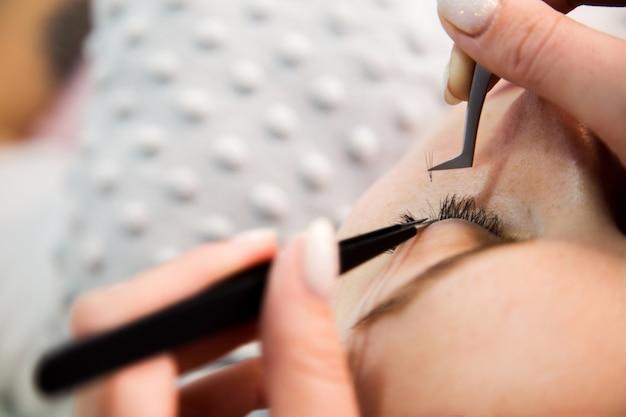 まつげエクステ手順。まつげが長い女性の目。まつげ、クローズアップ、マクロ、セレクティブフォーカス。