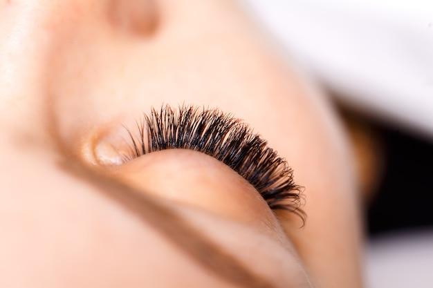 まつげエクステの手順。長いまつげを持つ女性の目。まつ毛、クローズアップ。