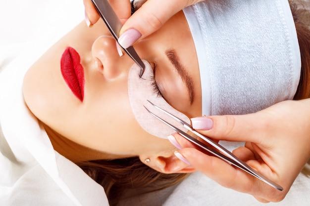 Eyelash extension procedure. woman eye with long eyelashes. lashes