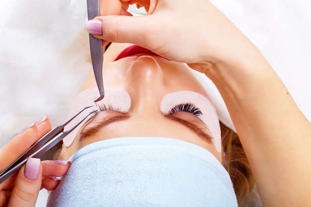 Eyelash extension procedure. woman eye with long eyelashes. lashes