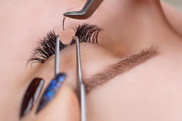 Eyelash extension procedure. woman eye with long eyelashes
