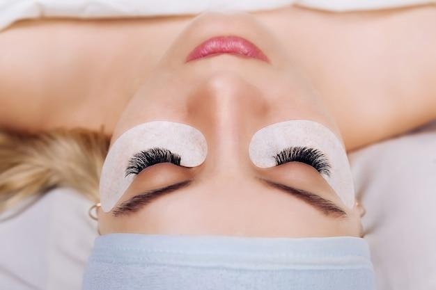 Eyelash extension procedure woman eye with long eyelashes