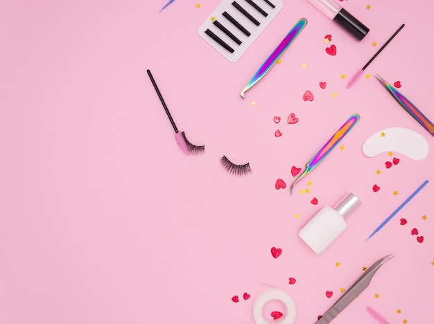 Eyelash extension tools, artificial eyelashes and red hearts on pink