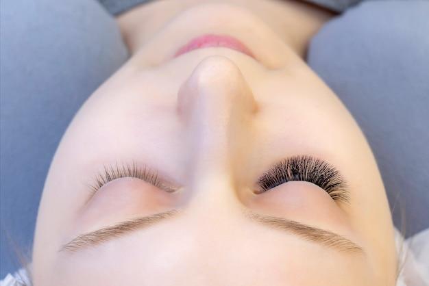 속눈썹 연장. 확장 된 속눈썹이 있고 확장 된 속눈썹이없는 눈의 근접 촬영. 이전과 이후