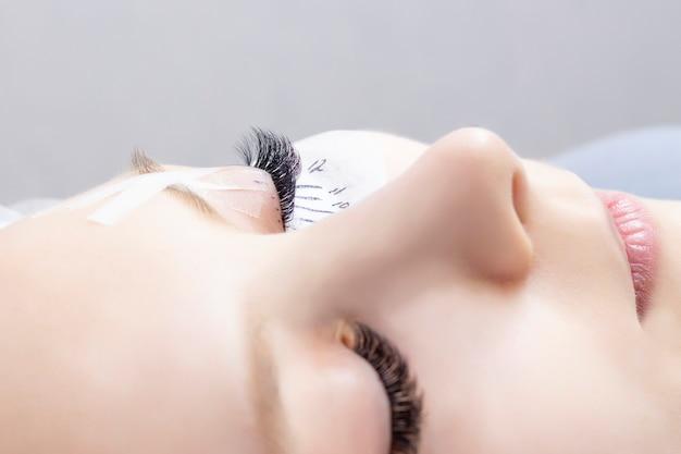 속눈썹 연장. 확장 된 속눈썹이 있고 확장 된 속눈썹이없는 눈의 근접 촬영