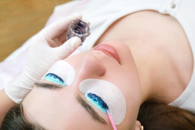 Ламинирование ресниц. окрашивание ресниц в салоне для молодой красивой женщины.
