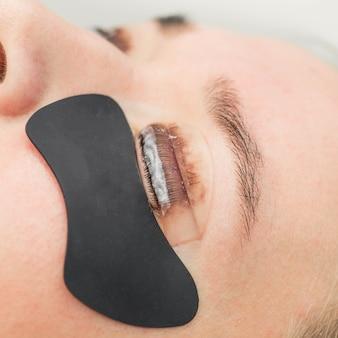 Eyelash lamination procedure. staining, curling, laminating, lash lift. eyelash extension. lengthening lashes for girl in beauty salon