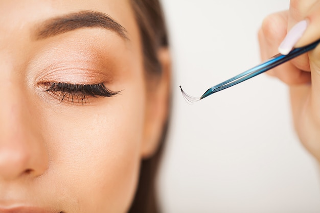 Eyelashes extensions. fake eyelashes. eyelash extension procedure. professional stylist lengthening female lashes. master and a client in a beauty salon
