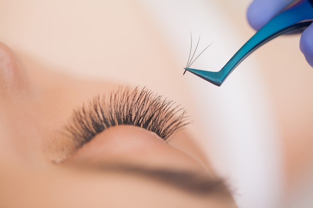 Eyelashes extensions. fake eyelashes. professional stylist lengthening female lashes.