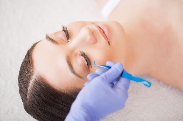 Eyelashes extensions. fake eyelashes. professional stylist lengthening female lashes.