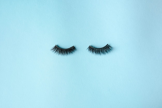 Eyelashes on light blue background, flat lay. space for text
