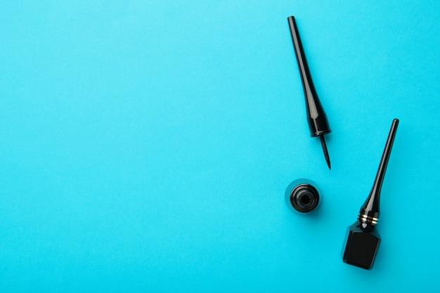 コピースペースと青い背景のアイライナー。上面図。美容コンセプト