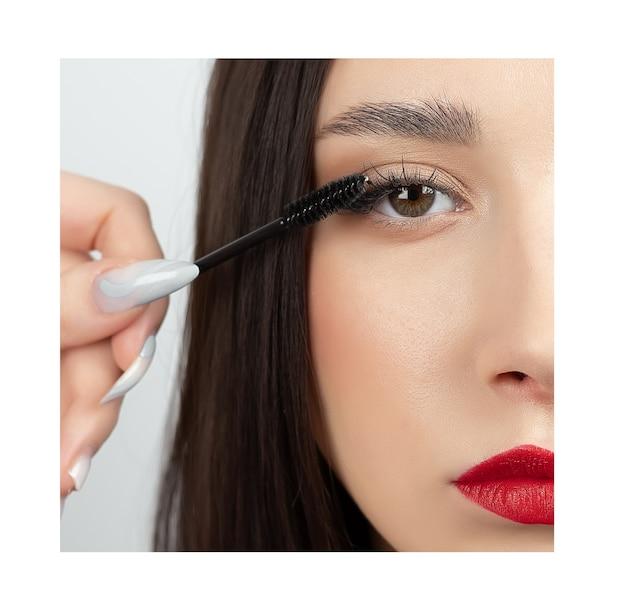 目と眉毛のクローズアップ。美しいメイク、長いまつげ、健康的なきれいな肌を持つ魅力的な女の子の肖像画。目の近くはブラシです。
