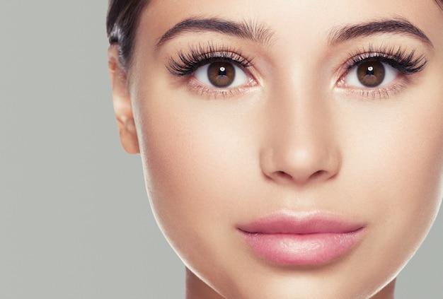 눈 속눈썹 여자 얼굴 자연 메이크업 건강한 피부를 닫습니다. 스튜디오 촬영. 색상 배경입니다.