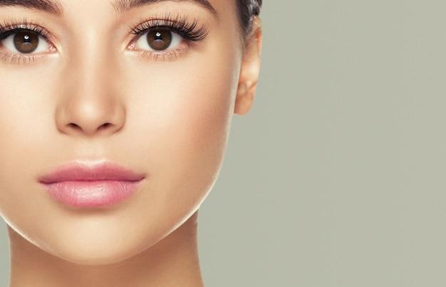 Глаза ресницы лицо женщины крупным планом естественный составляют здоровую кожу. студийный снимок. цвет стены.